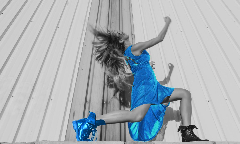 Dancer in black dress performing movements.